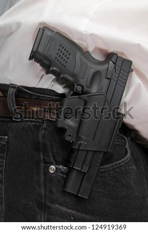 Pistol Packing/close up of holstered handgun against plain white shirt & black denim