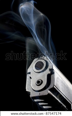 pistol that is smoking with a black background and muzzle lighting