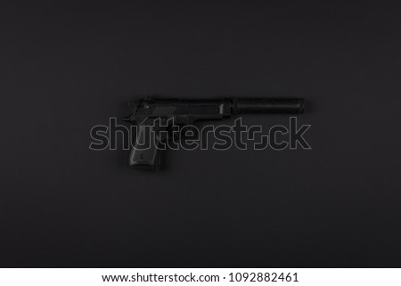 pistol with a silencer on a black isolated background #1092882461