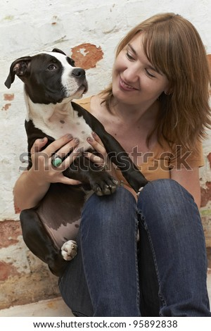Pit Bull puppy sitting on lap of an attractive young lady
