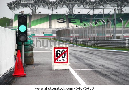 Pit stop exit with speed limit signboard and traffic light. Concept of safety measures for motor sport participants.