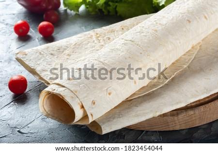 Pita bread is thin on a wooden Board. Armenian thin pita bread on a wooden Board. Pita bread for Shawarma. Stockfoto ©