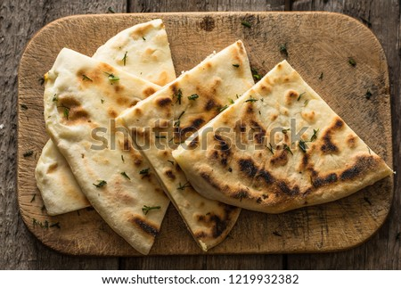 Pita bread on wooden board with feta cheese and tomatoes and pepper. Still life of food. Georgian cuisine. Spanish food. National cuisine. Traditional dish on wooden table. Mediterranean cuisine.