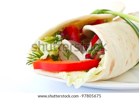 pita bread stuffed with vegetables on white background
