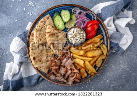 Pita shawarma with olive oil, meat, potatoes and vegetables. Natural delicious food. Greek cuisine menu. Still life in a marine style on a blue background. Stockfoto ©