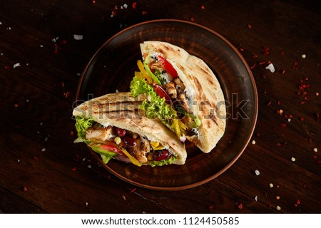 Pita stuffed with chicken, beans and letucce on clay plate over wooden background, top view, selective focus. Stockfoto ©