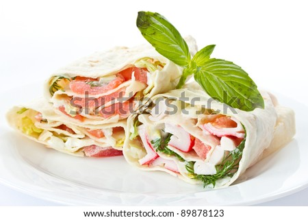 pita stuffed with fish in a white plate