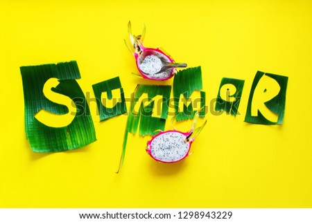 Pitahaya fruit and word SUMMER letters from green tropical palm leaves on yellow textured background. Original idea from natural material for summer design. Flat lay #1298943229