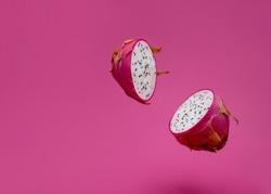 Pitaya or dragon fruit levitate on pink background.