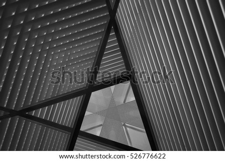 Pitched roof or ceiling. Reworked close-up photo of sloped walls. Realistic though unreal industrial interior. Abstract black and white background image on the subject of modern architecture. #526776622