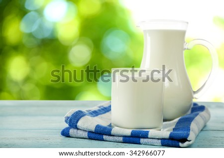 Pitcher and glass of milk on bright background #342966077
