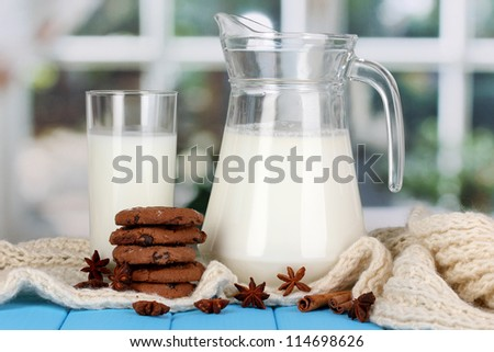 Pitcher and glass of milk with cookies on crewnecks knitwear on wooden table on window background