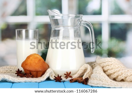 Pitcher and glass of milk with muffins on crewnecks knitwear on wooden table on window background