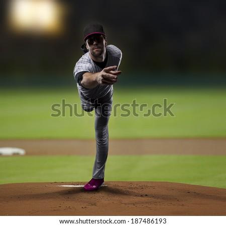 Pitcher Baseball Player on a Pink Uniform on baseball Stadium.
