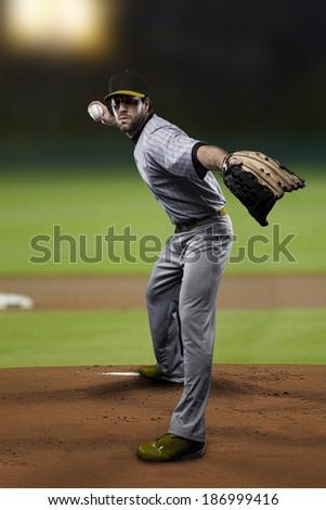 Pitcher Baseball Player on a Yellow Uniform on baseball Stadium.