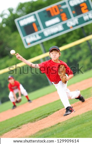 Pitcher throwing the ball to the batter with a funny face.  Has the scoreboard in the background, and ball mid air.