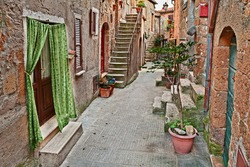 Pitigliano, Grosseto, Tuscany, Italy: old alley with ancient houses and plants in the picturesque medieval town