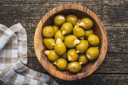 Pitted green olives stuffed with almonds in bowl on wooden table. Top view.