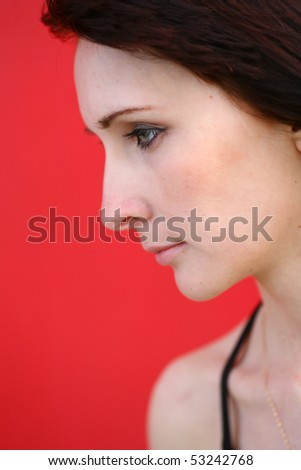 Pityful lady. Latina girl is posing against a red wall with copy space, vertical image. Portrait of a melancholic caucasian woman with brown hair and blue eyes over a red background.
