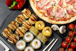 Pizza and sushi rolls tempura and bake rolls on the background of ingredients .Pizza, sushi food photo for menu. Combo set of rolls and pizza.
