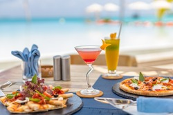 Pizza and tropical cocktail with beautiful sunny vacation infinity swimming pool ocean view. Beach restaurant, sea view, glasses, plates, food, tropical cocktail, blur loungers, chairs, sun umbrellas