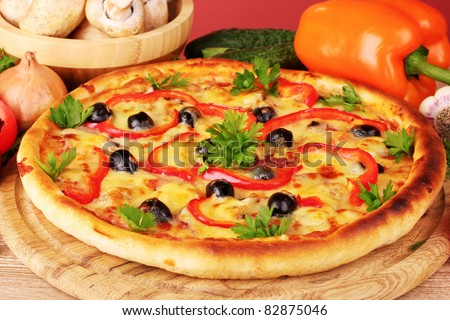 pizza and vegetables on red background