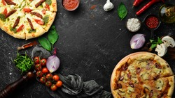 Pizza background. Set of delicious homemade pizzas. On a black background.