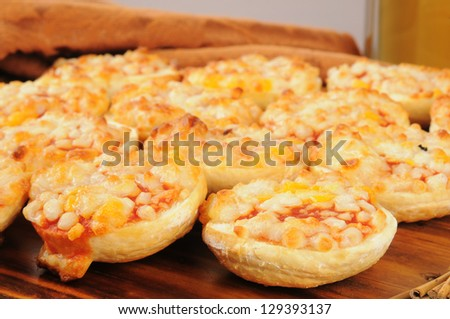 Pizza bagels with beer in the background - close up, shallow depth of field with focus on front bagel