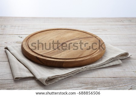 Pizza board and canvas napkin with lace on wooden table. Top view mock up