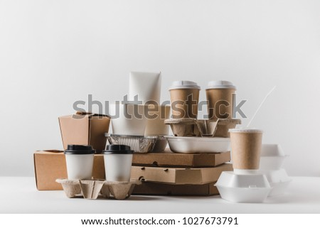 pizza boxes and disposable coffee cups with take away boxes on tabletop