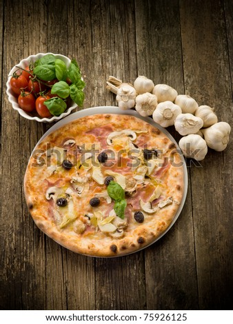 pizza capricciosa on dish over wood background