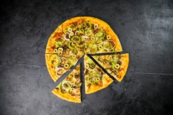 Pizza caseira deliciosa com ingredientes na mesa de madeira rústica com fundo escuro.