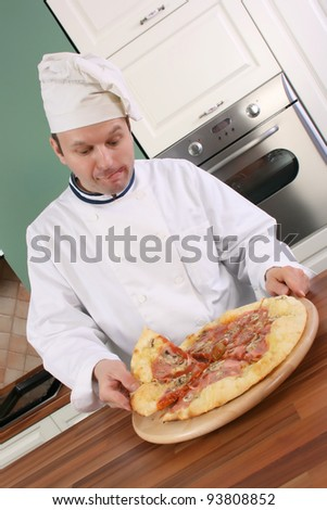 Pizza chef holding slice of pizza and with face expression shows that he is very hungry