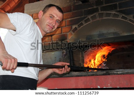 Pizza Chef. Pizza being baked in a wood fire brick oven in a restaurant.