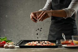 Pizza cooking recipe made by chef on a black wooden table - parmesan, olive oil, tomatoes, spices and herbs. Concrete wall for text or design. Horizontal view.