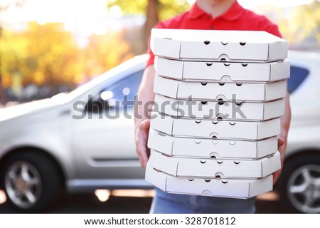 Photo of Pizza delivery boy holding boxes with pizza near car