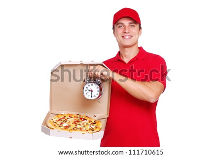 Pizza delivery courier in red uniform holding the pizza and the two bells alarm clock