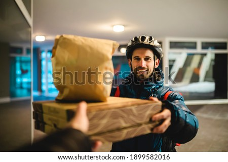 Pizza delivery home. The courier with the bicycle helmet delivers the hot food. Takeaway pizza, food delivery. Stock photo ©