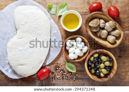 pizza dough and components for preparation homemade  hot rural health pizza. Food ingredients on the wooden background. small mozzarella, mushrooms, green and black olives #294371348