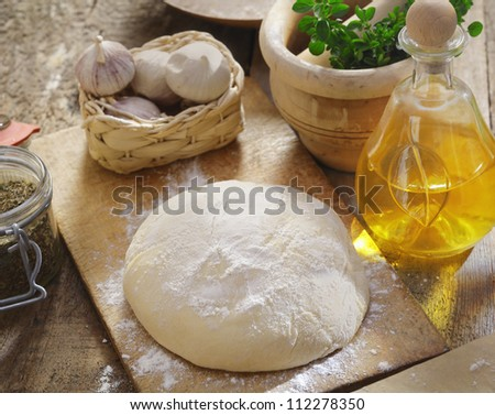 Pizza dough being left to rise surrounded by fresh herbs, garlic and ingredients in the kitchen