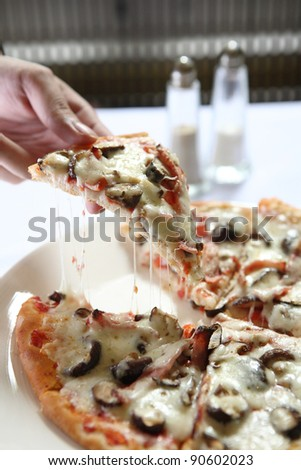 Pizza ham ans mushroom slice lifted with cheese strings