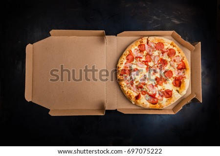 Pizza in a cardboard box against a dark background. Space for text. View from above. Pizza delivery. Pizza menu.
