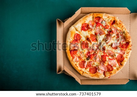 Pizza in a cardboard box on a green chalkboard background. Space for text. View from above. Pizza delivery. Pizza menu.