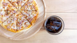 Pizza in a wooden tray and soft drink. Eat fat not good for health. Concept Junk food,  on wood white background. Blank for design.