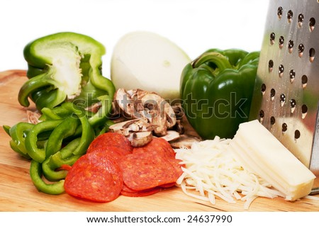 Pizza ingredients on wooden cutting board.  Isolated on white background.