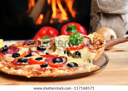 Pizza lifting slice with pepperoni and olives