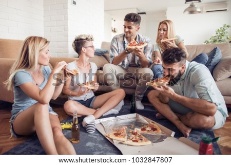 Pizza lovers.Group of playful young people eating pizza while having fun together. #1032847807