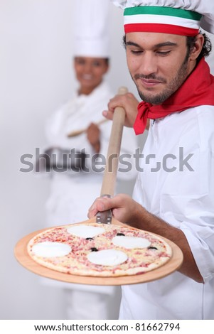 Pizza man and female cook in the background - stock photo