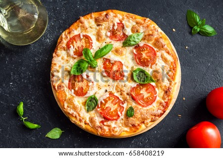 Pizza Margherita on black stone background. Homemade Pizza Margarita with Tomatoes, Basil and Mozzarella Cheese.
