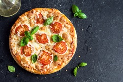 Pizza Margherita on black stone background, top view. Pizza Margarita with Tomatoes, Basil and Mozzarella Cheese close up.
